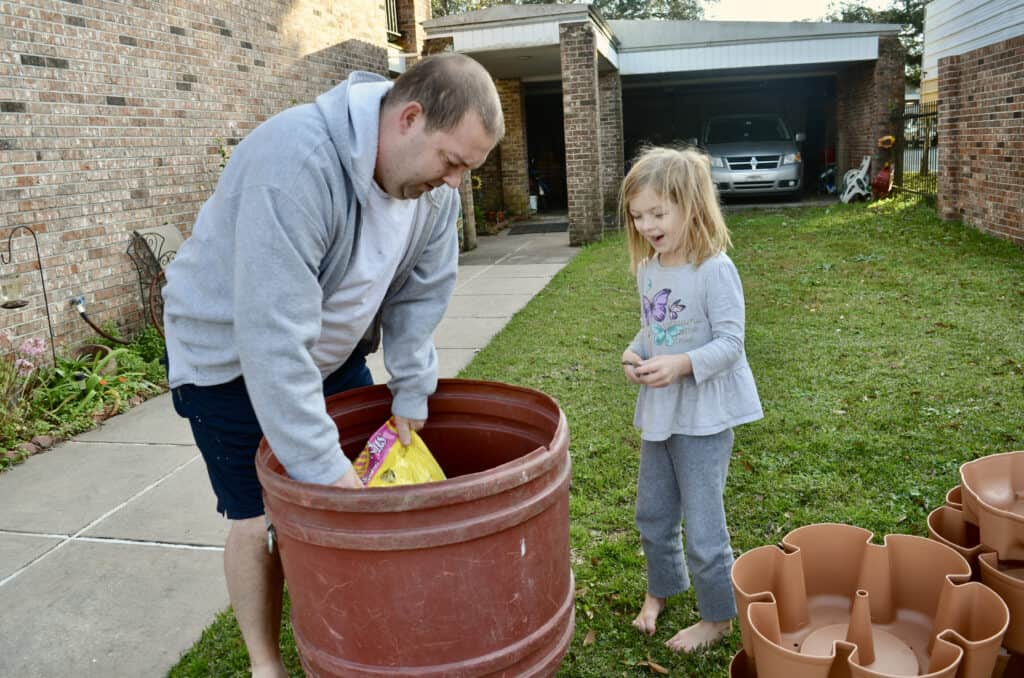 little girl pouring dirt with dad