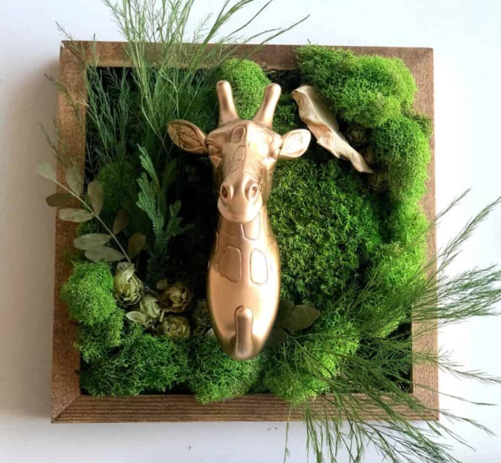 gold giraffe in green planter frame