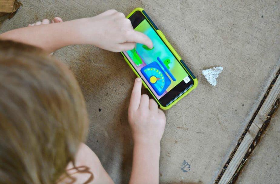 girl playing Noggin app outside