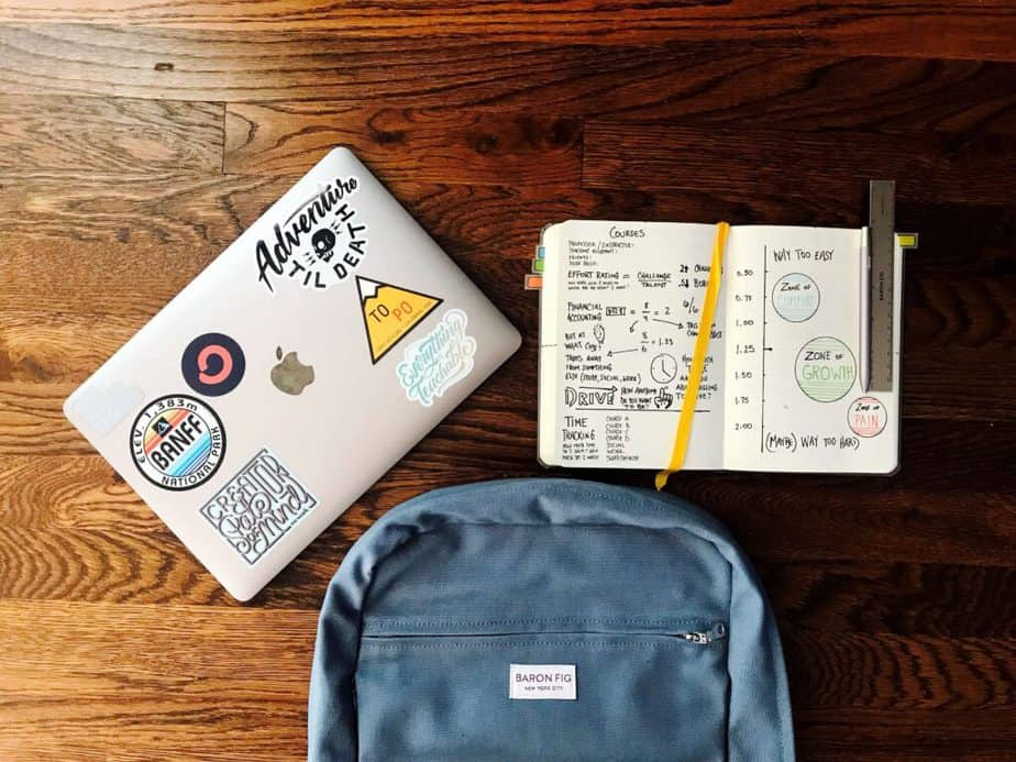 backpack and laptop on wood table